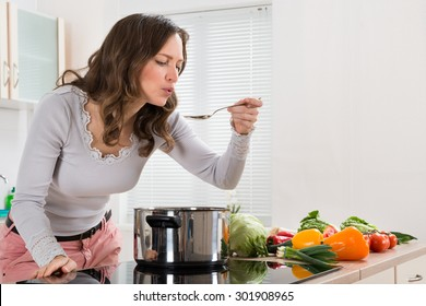 Young Woman Tasting Food With Spoon In Kitchen