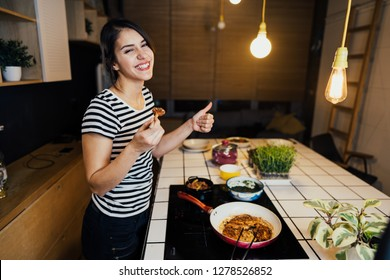 Young woman tasting a healthy meal in home kitchen.Making dinner on kitchen island standing by induction hob.Preparing fresh vegetables,enjoying spice aromas.Eating in.Passion for cooking.Dieting