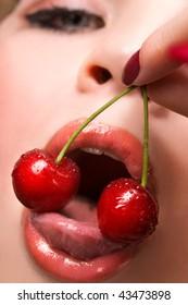 Young woman tasting red cherries macro