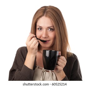 Young woman tasting from a teaspoon and holding a cup,isolated on white