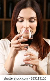 Young woman tasting wine in cellar