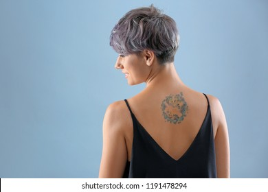 Young woman with tattoo on color background. Space for text