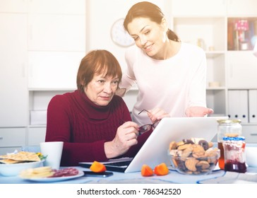 Young woman at tea table using laptop with mature mother at home