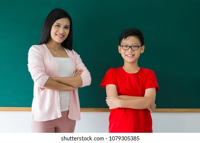Young woman teacher and boy student standing on chalk board , Education concept
