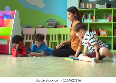 young woman teacher in duty of teaching preschool kids boys in classroom, playing enjoying in learning together