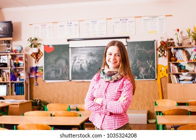Young woman teacher posing on a background class