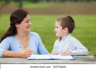 Young woman teacher teaches little young boy in white shirt writing or drawing with a pencil on a sheet of paper on wood table in the park