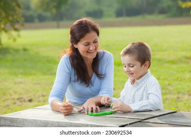 Young woman teacher teaches little young boy in white shirt painting with the brush to make  pasta beads