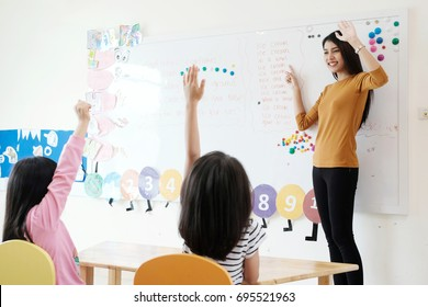 Young woman teacher teaching kids in kindergarten classroom, preschool education concept