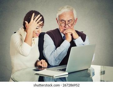Young woman teaching confused, senior, older, elderly man with eyeglasses how to use laptop. Generation gap differences concept