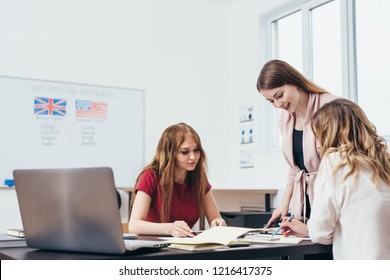 Young woman teaching English to adult students at language school.