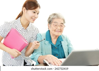 Young woman teaching old woman to use laptop