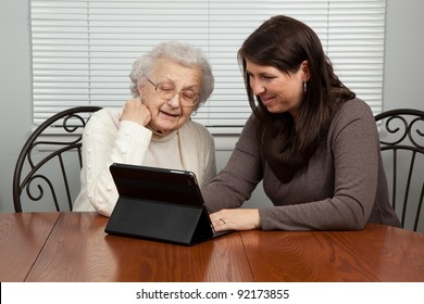 Young Woman Teaching Senior Woman How to Use a Tablet PC