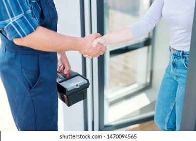 Young woman and technician saying goodbye while shaking hands after repair work