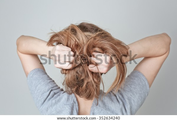 Young woman teen girl pulling her long light hair on white background
