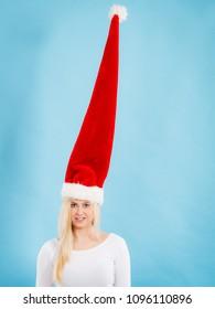 Young woman teen girl wearing blowing windblown santa claus hat. Crazy joyful girl having fun. Christmas time. Studio shot on blue