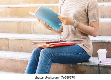 Young woman teenager students  with books sit on stair