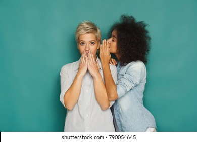Young woman telling her girlfriend some secret. Two women gossiping. Excited emotional girl whispering to her friend ear, turquoise studio background