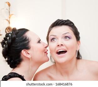 Young woman tells her friend a big secret