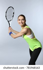 Young woman with tennis racket on light background
