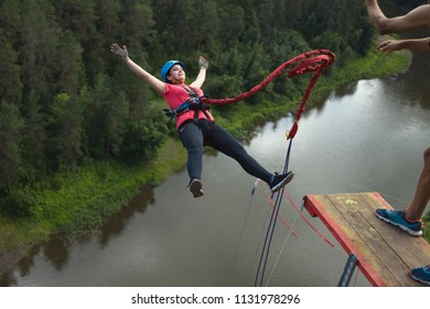 Young woman, tethered to a safety rope, falls from a great height into a deep canyon on the background of a river, close-up. Ropejumping.