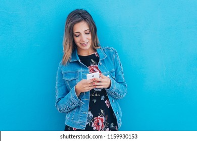 Young woman texting on her smartphone with a look of concentration as she stands against a blue wall
