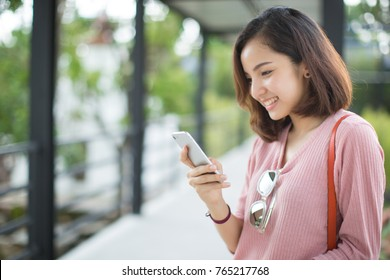 young woman texting on the smart phone in the street