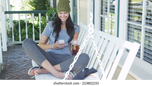 Young woman texting and sitting on porch