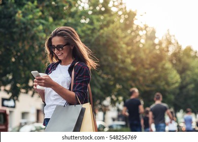 Young woman texting while enjoying a day shopping