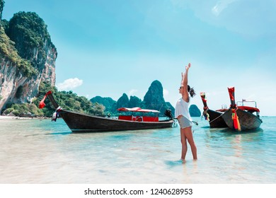 Young woman with thailand longtail boats on a beach