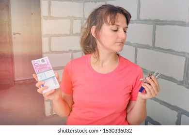 A young woman is thinking about buying a new apartment. The keys and a bundle of Euro notes in his hands. The girl looks at the keys to the built house and wants to buy it for cash money.