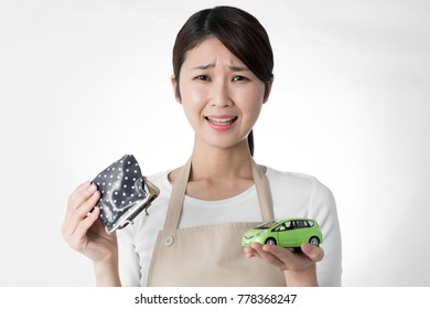 Young woman thinking about car and money.