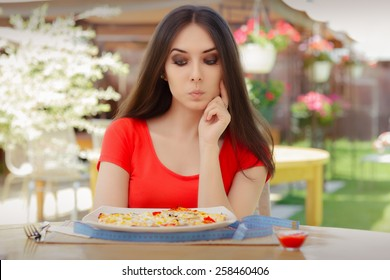Young Woman Thinking About Eating Pizza on a Diet - Beautiful girl Making Nutrition Decisions in a Restaurant