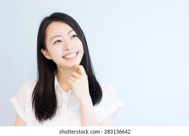young woman thinking against light blue background