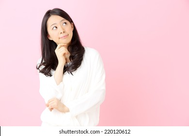 young woman thinking against pink background