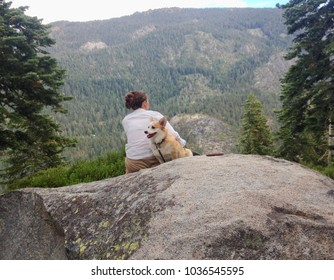 Young woman thinking while sitting on a boulder with Corgi dog by her side in mountains. Behind view, with mountains in distance. Woman is framed by two evergreen trees. Color, landscape photo.