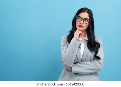 Young woman in a thoughtful pose on a blue background
