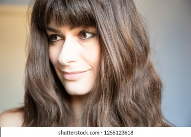 Young woman three quarters close-up portrait. Caucasian with brown long hair and bangs. Smiling expression, looking down.