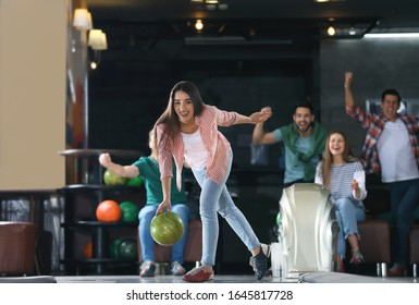 Young woman throwing ball and spending time with friends in bowling club