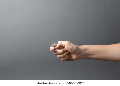 Young woman throwing coin on grey background, closeup