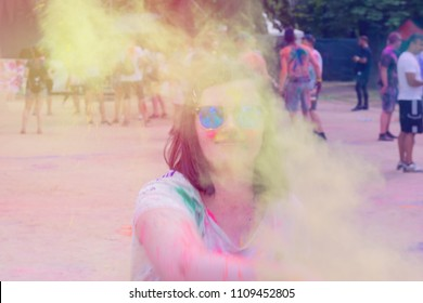 A young woman throwing color powder towards the camera at holi festival - dusty soft focus