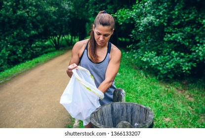 Young woman throwing garbage into a trash can after plogging