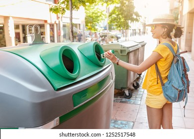 young woman throwing garbage in recycling bin at city street