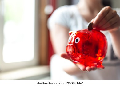 Young woman throwing money in a red piggy Bank