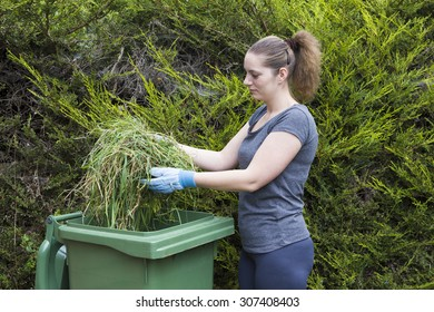 Young woman throwing out grass in green bin for garden waste