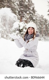 young woman throwing snow  in the air in park