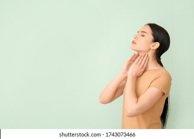 Young woman with thyroid gland problem on color background
