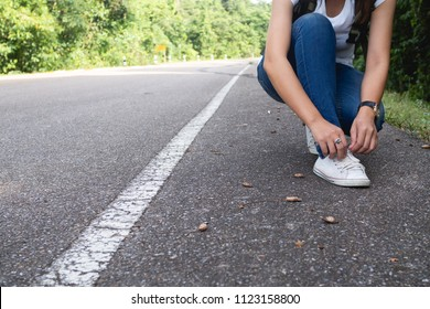 Young woman Tie a rope boots on the road.