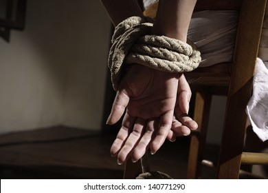 Young woman tied to a chair in a empty room, hands close up