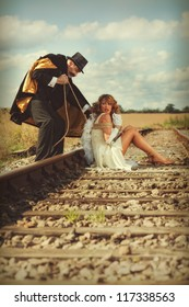 Young woman tied to railway track by villain